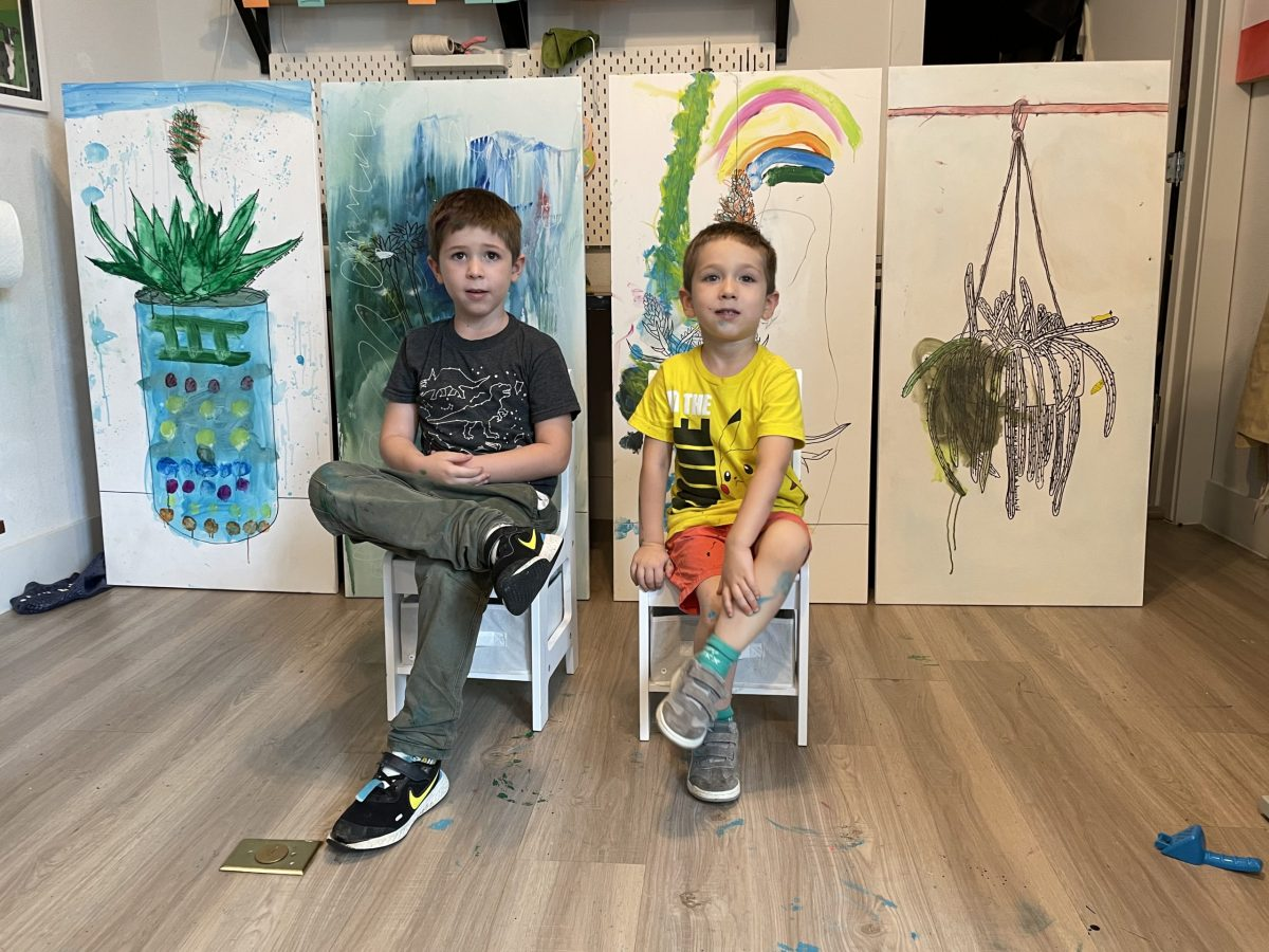 Rodrigo, 6, and his brother Emiliano, 3, sit in front of illustrations they created in collaboration with their mother, Daniela Oliver de Portillo.