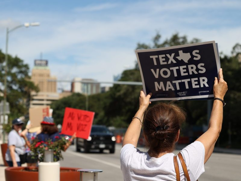 """A woman holds up a sign that reads """"Texas Voters Matter"""" as cards pass by on Market Street. The """"Save Our Democracy"""" rally was hosted by SATX Indivisible in front of the entrance to the Lila Cockrell Theather."""