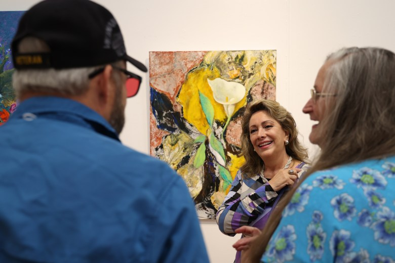 Carmen Oliver (center) smiles while speaking with one of her painting students, Wilanna Ashley (right), and her husband, Wayne, at the opening of <i>Botanical Sensations</i>, Friday evening.