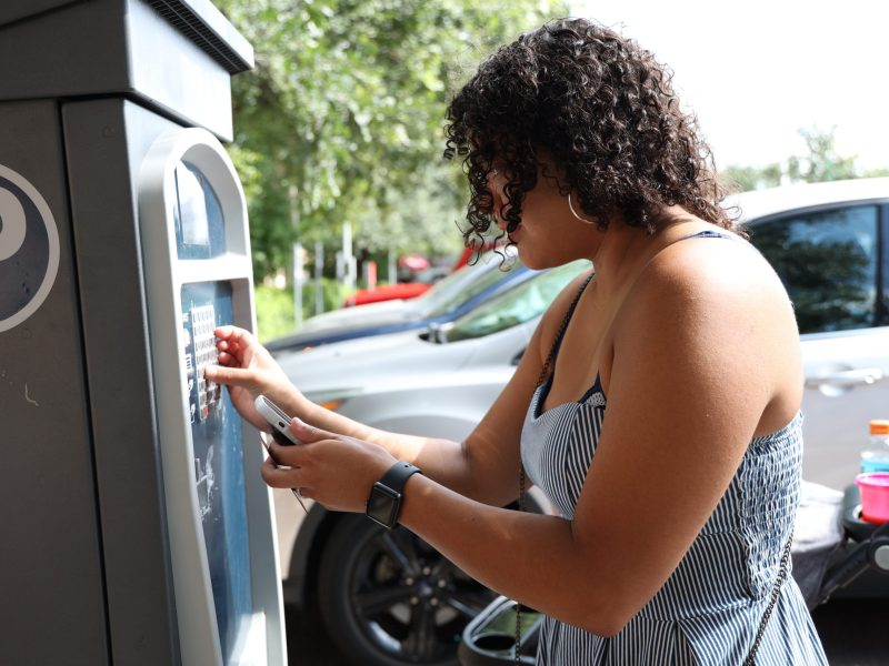Emily Wanger pays for parking using a meter in one of the premium parking lots at the Pearl Saturday.