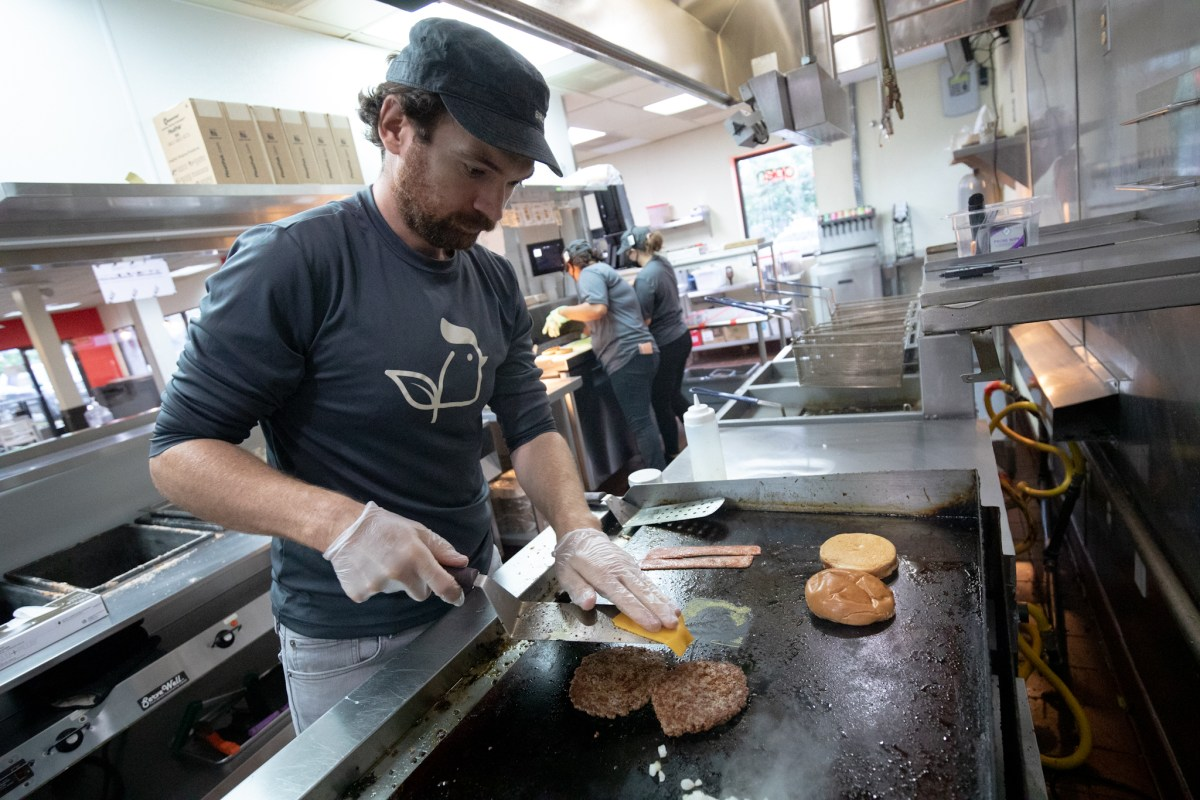 Lucas Bradbury, owner of Project Pollo, works the grill where the vegan-centric fast-food chain uses Impossible Meat instead of traditional beef for hamburgers.