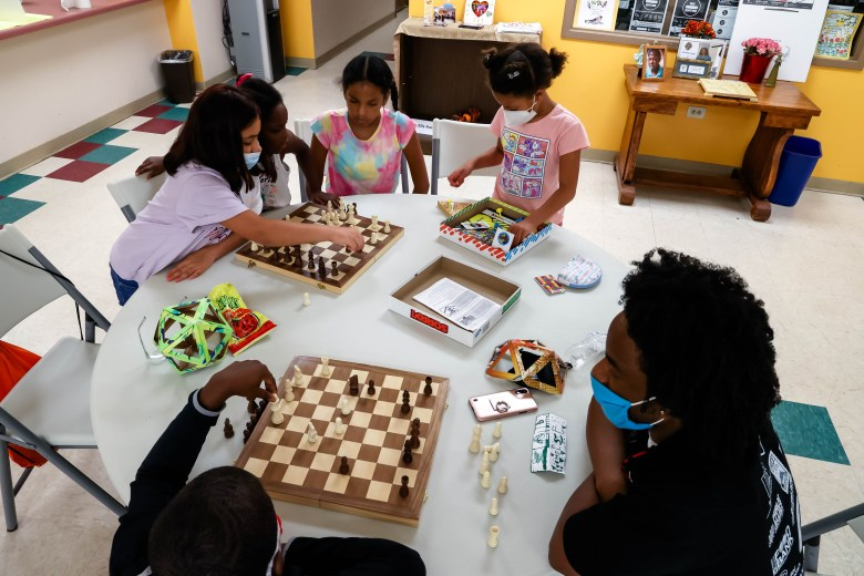 A group of children play chess and other board games at the Ella Austin Community Center, Tuesday.
