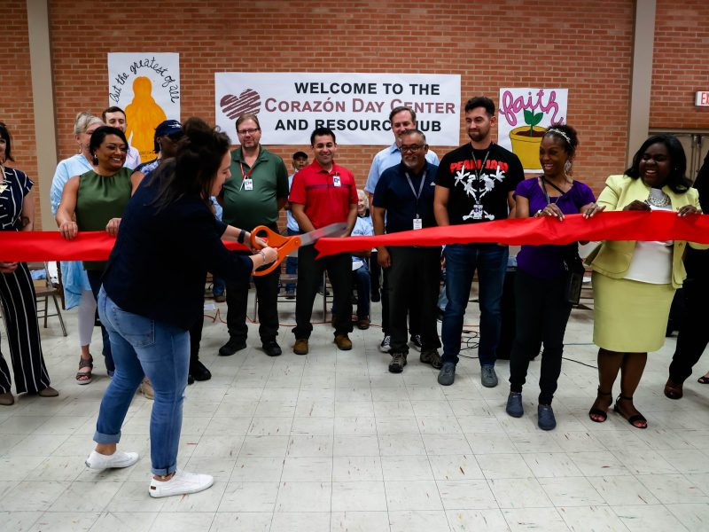 Morgan Handley, associate director for Corazón, cuts the red ribbon with ceremonial scissors marking the official opening of the organization's new homeless day center on Thursday.