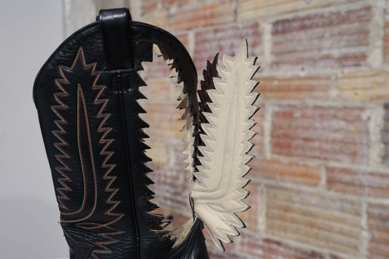 This boot sculpture is titled Bota Para Llegar al Cielo. Villalobos cutout the outlihne of the decorative stitching and opened them up to create a wing effect on the boot.