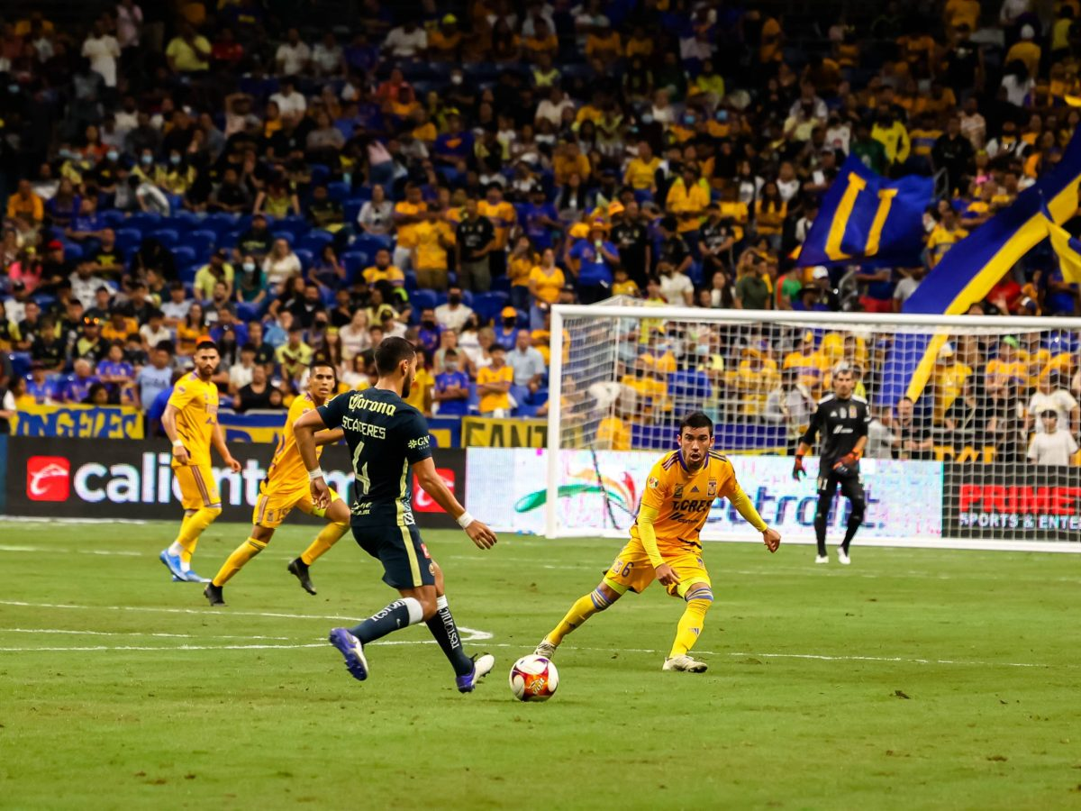 Tigres UANL defensive midfield, Diego Madrigal, rushes Club América defender center-back, Sebastián Enzo Cáceres, during the Liga MX friendly match at the Alamodome on Saturday.