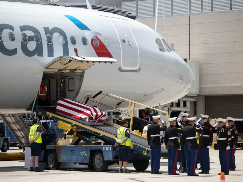 The flag-laden coffin carrying Marine PFC JL Hancock slides down the conveyor belt from the hold after traveling on commercial American Airlines flight 1967. U.S. Marines wait at attention to deplane the casket and transfer it to the hearse.
