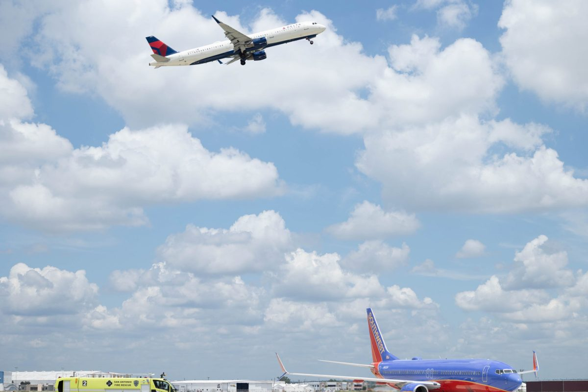 A Delta flight takes off above as a Southwest flight taxies on the tarmac at the San Antonio International Airport.