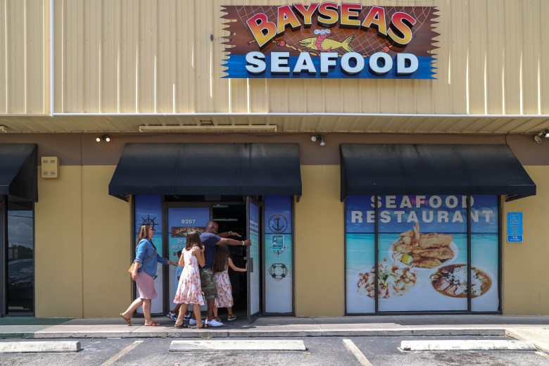 Craig Ball walks inside of Bayseas Seafood with his wife, Wendy, and three children, Ava, Adrianna and Solomon Thursday.