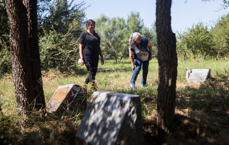 Rose Hernandez, left, looks at headstones with her mother, Oralia, in an abandoned cemetery in Guadalupe County on Sunday.