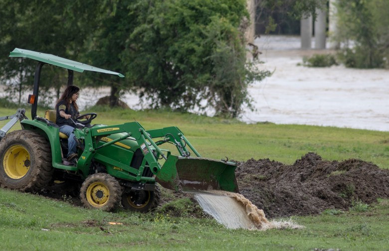 Veronica Law uses a tractor to remove floodwater from her property on Tuesday.