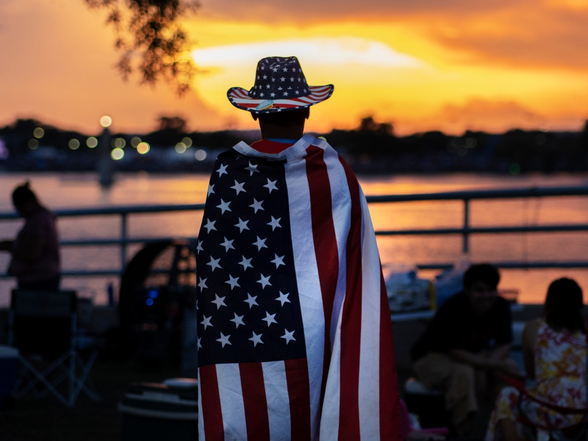 Thomas Zurita waits for the start of the fireworks display during the Fourth of July Celebration at Woodlawn Lake Park on Sunday.
