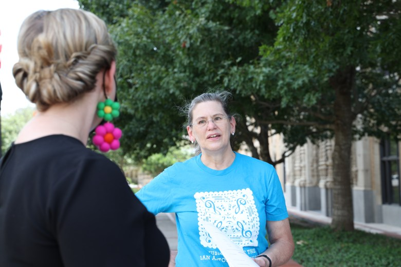 Mary Ellen Goree, principal second violin for the San Antonio Symphony and Chair of the players committee in San Antonio Symphony Musicians, speaks with an arts supporter in front of the Tobin Performing Arts center Saturday.
