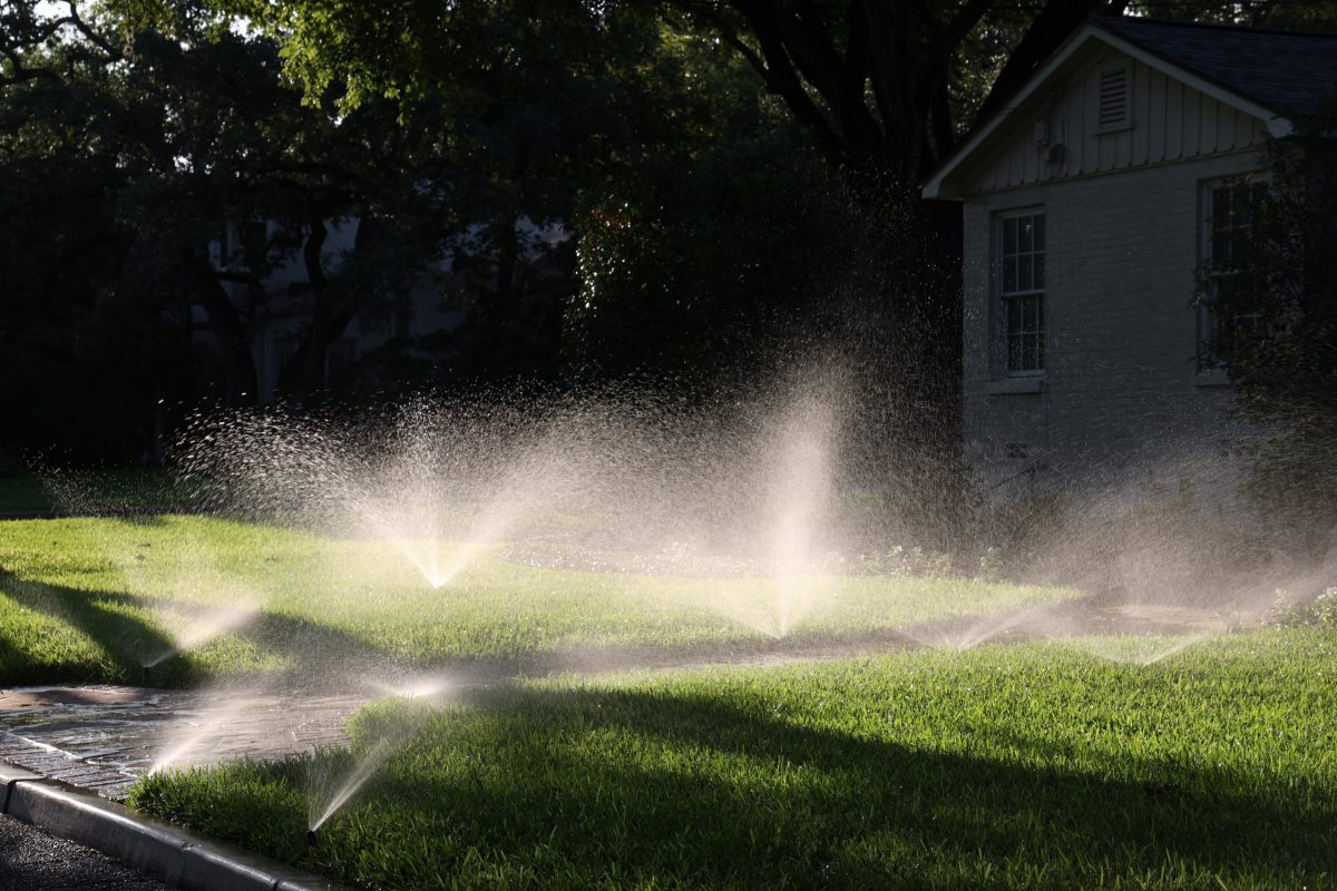 Sprinklers water the lawn in front of an Alamo Heights home Tuesday.