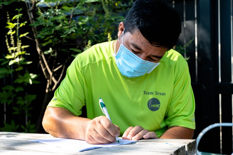 Mohammed Rezai fills out a form provided by The Center for Refugee Services to gather information about the family members they are trying to help escape Afghanistan.