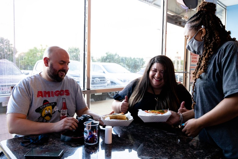 Krytal Cross, owner of A Chicago Bite, serves Cherise and Lucas the Chicago Dog. A Chicago Bite opened on Evans Road in August.