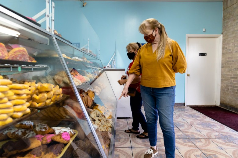 Velma Peña bumps into her son's mother-in-law, Betty Beltoro, while visiting Mario's Bakery.