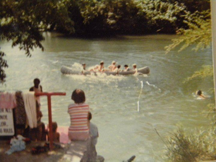 A group of children are canoeing in the Guadalupe River.