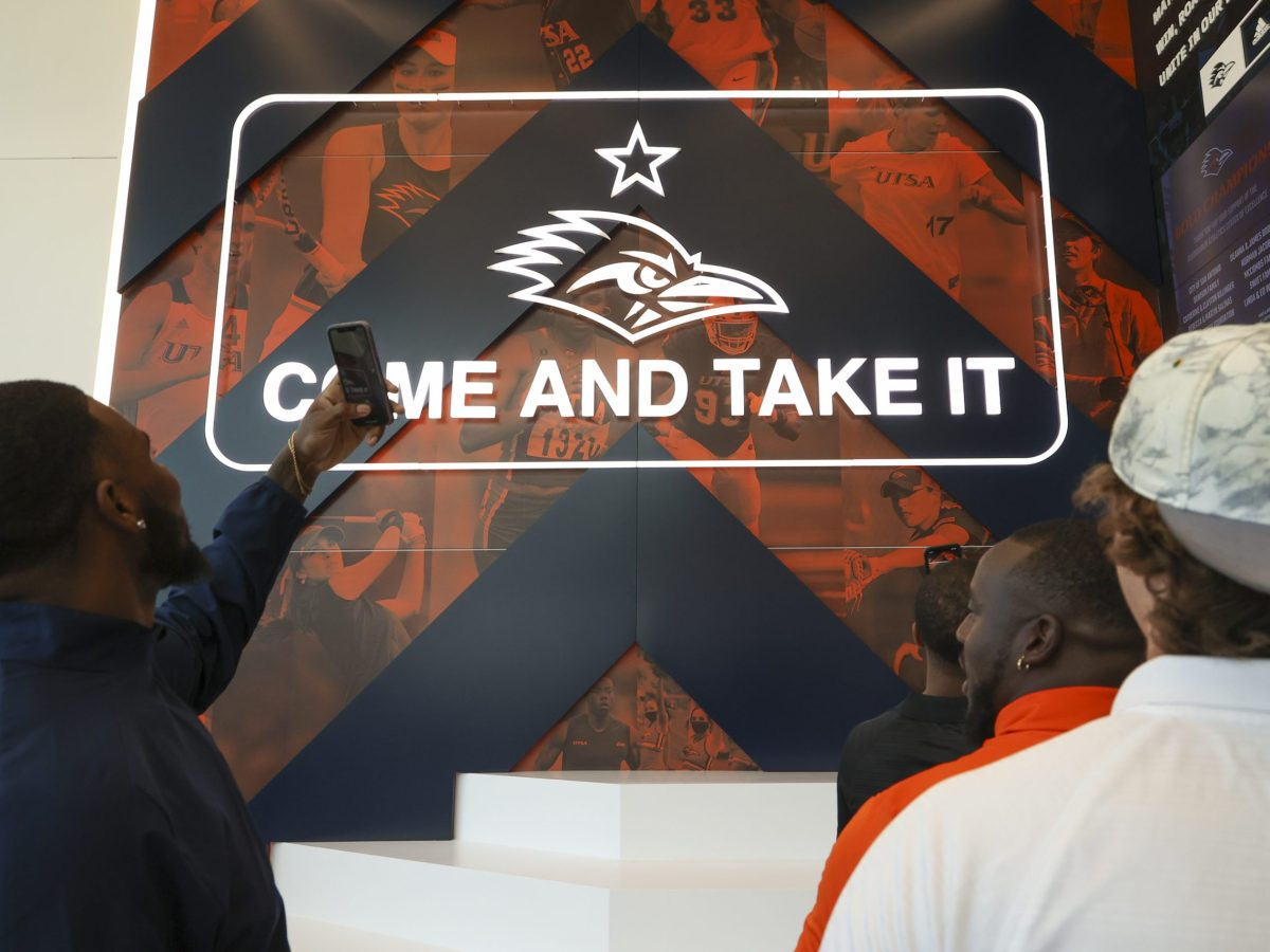 UTSA athletes photograph the entrance to the new Roadrunner Athletics Center of Excellence (RACE).