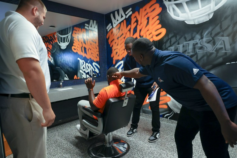 UTSA football players admire and interact with the new barber shop outside the men's locker rooms.