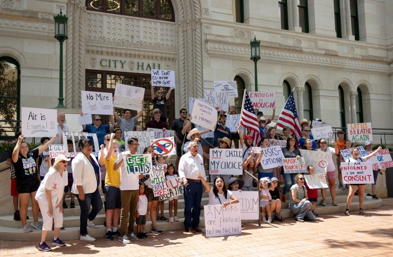 Protesters pose for a photo on the steps of San Antonio City Hall during a protest against wearing masks on Friday.