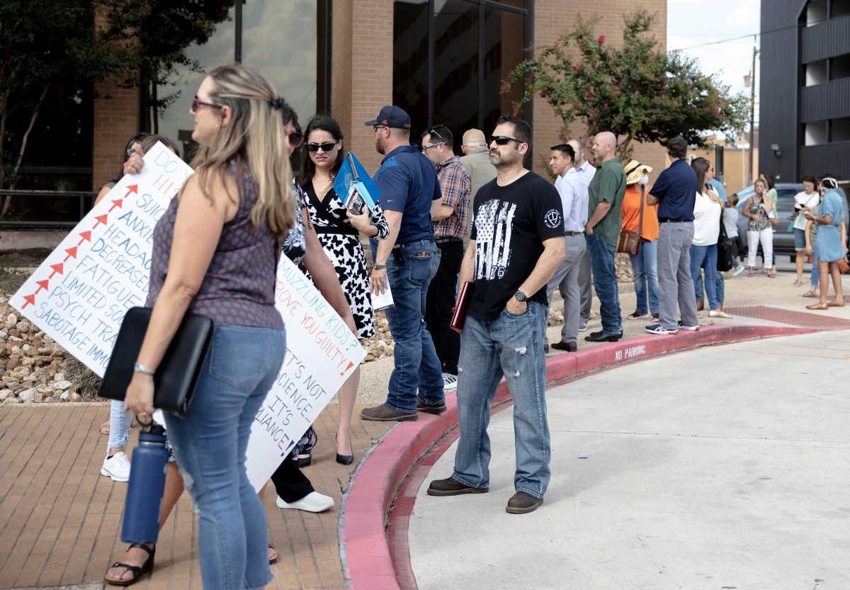 People line up outside of the North East ISD headquarters Thursday before an emergency meeting about mandating masks in schools.