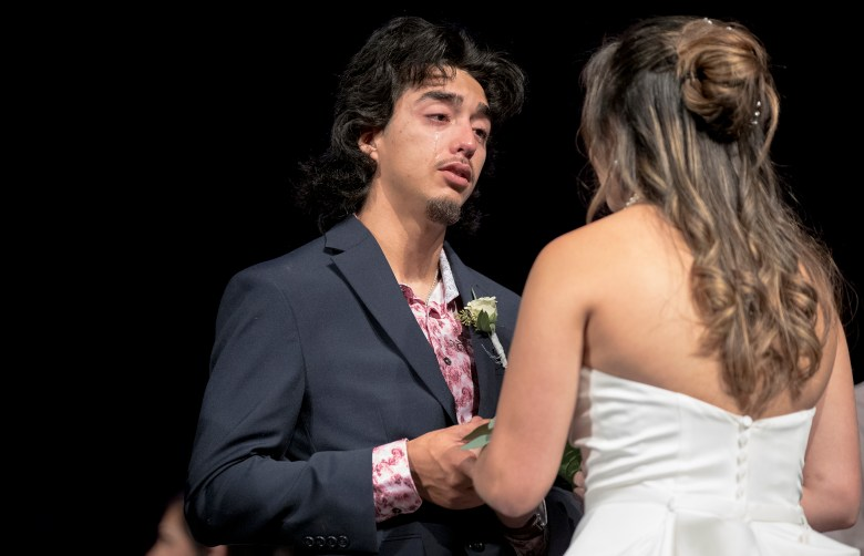 Abraham Lara cries while placing a ring on Bailey Goodwin's finger during a mass wedding ceremony at Community Bible Church on Saturday.