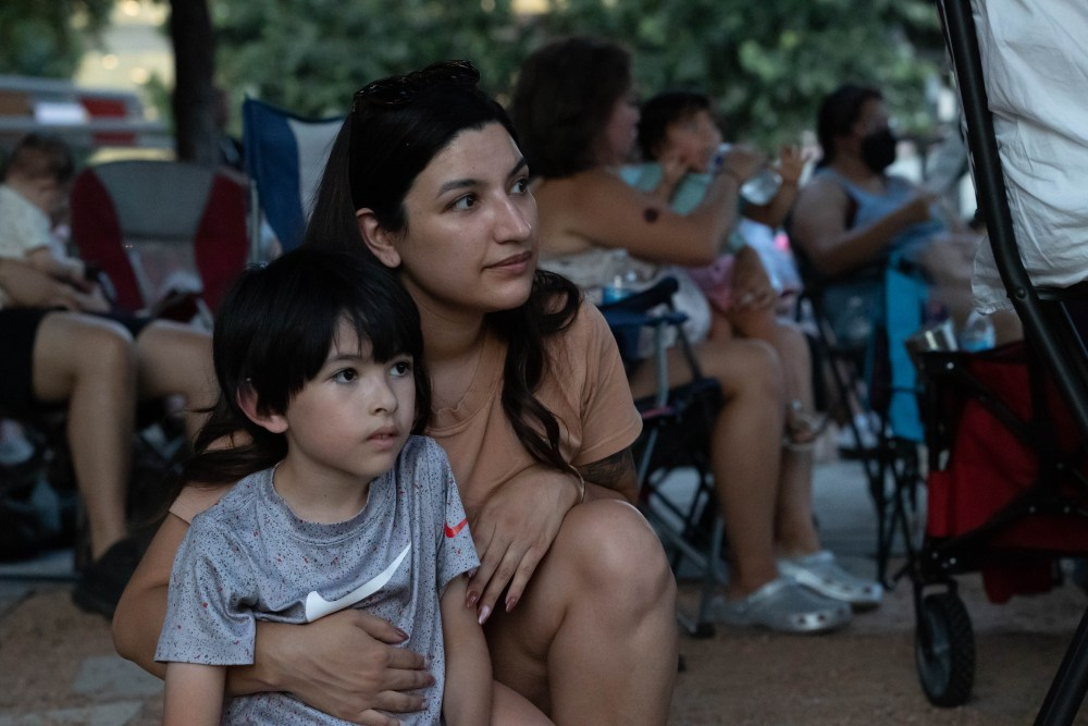 Mary Jane Lou watched the San Antonio Symphony with her seven-year-old son, Atom, during the free concert in Main Plaza Saturday evening.