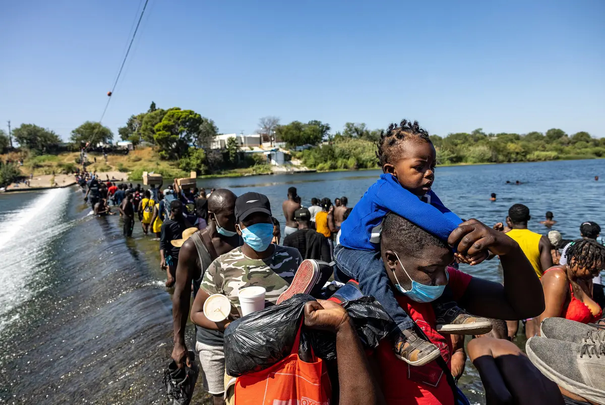 Migrants cross the Rio Grande between Del Rio and Ciudad Acuña on Friday to bring supplies back to a temporary migrant camp under the international bridge in Del Rio.