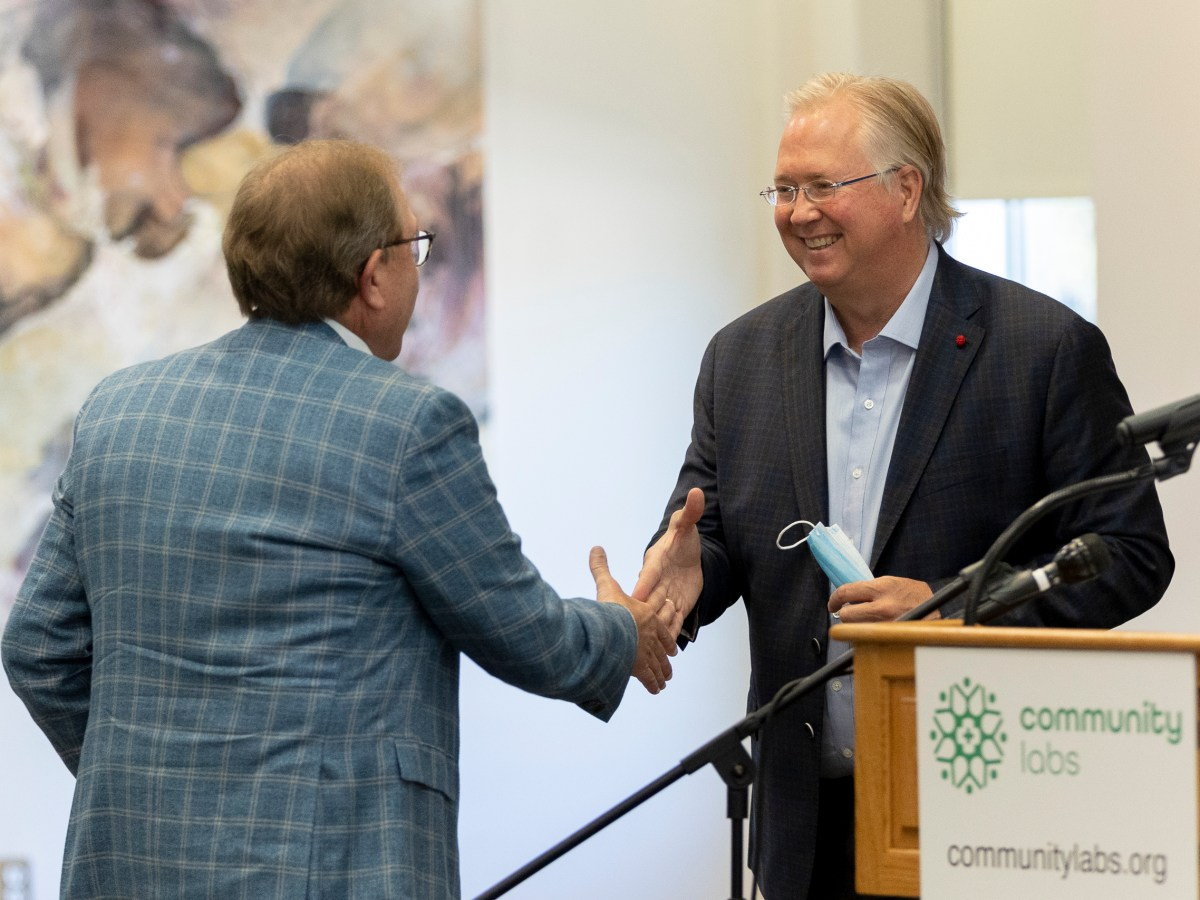CommunityLabs Co-Founder shakes hands with BioBridge Global CEO Marty Landon during the press conference announcing one million tests for COVID-19.