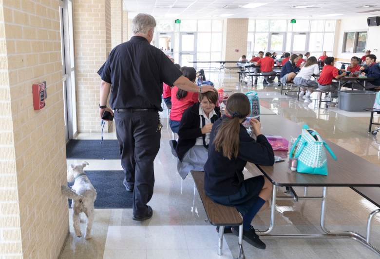 Father Pat O'Brien of St. Pius X greets students during lunch along with his schnauzer, Gabby.