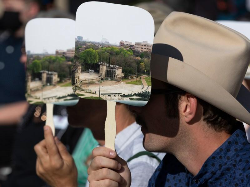 Garrett T. Capps holds a Sunken Garden Theater fan to block the sun on Friday morning.