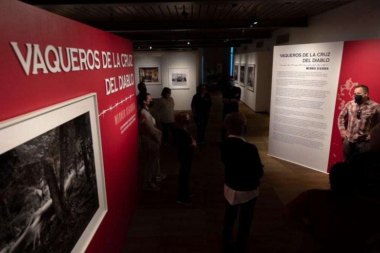 Photographer Werner Segarra, right, speaks to his exhibition Vaqueros de la Cruz Del Diablo during a docent briefing at the Briscoe Western Art Museum on Friday.