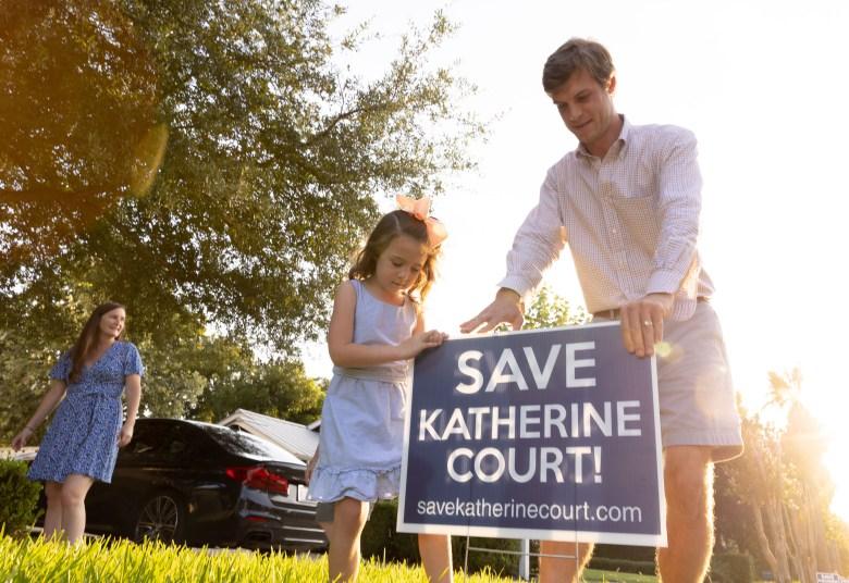 John, Elizabeth, and Clara, 4, Feitshans place yard signs opposing a development on Katherine Court.