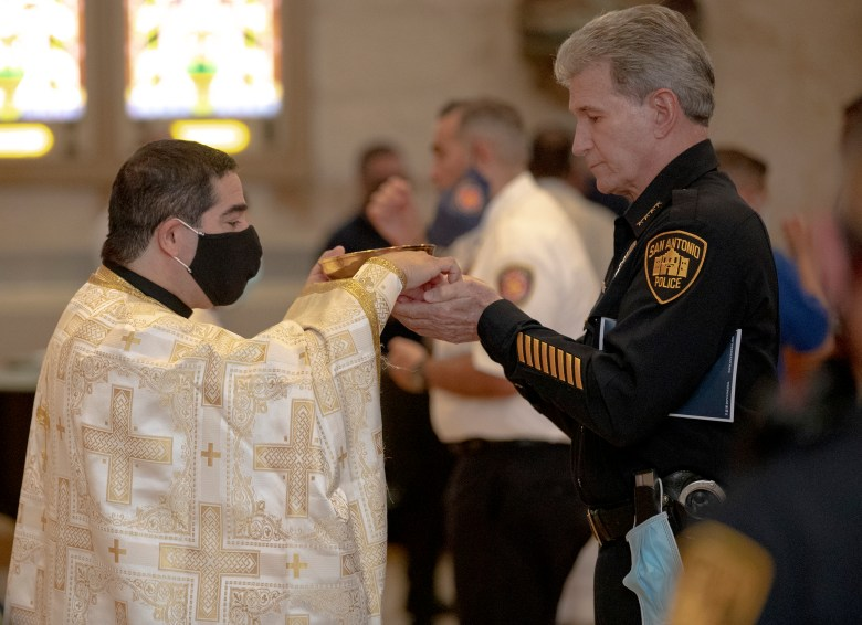 San Antonio Police Chief William McManus receives communion during a Blue Mass ceremony honoring law enforcement officers at San Fernando Cathedral on Wednesday.