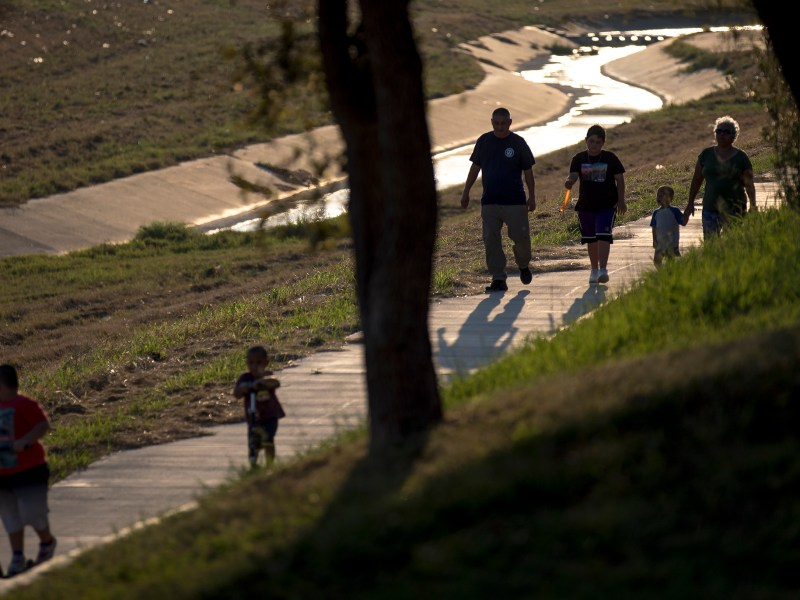 A family walks on the Apache Creek Trailway on Wednesday.