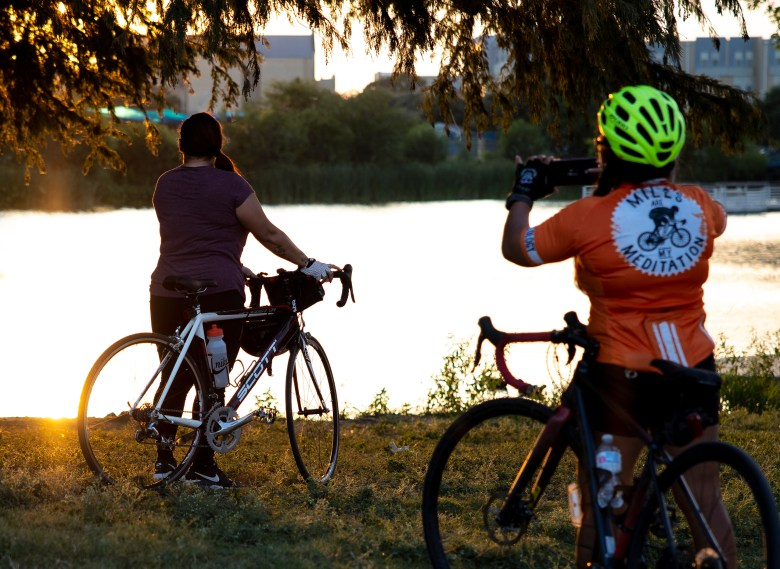 A bicyclist poses for a sunset photo with her bike near Elmendorf Lake on Wednesday.