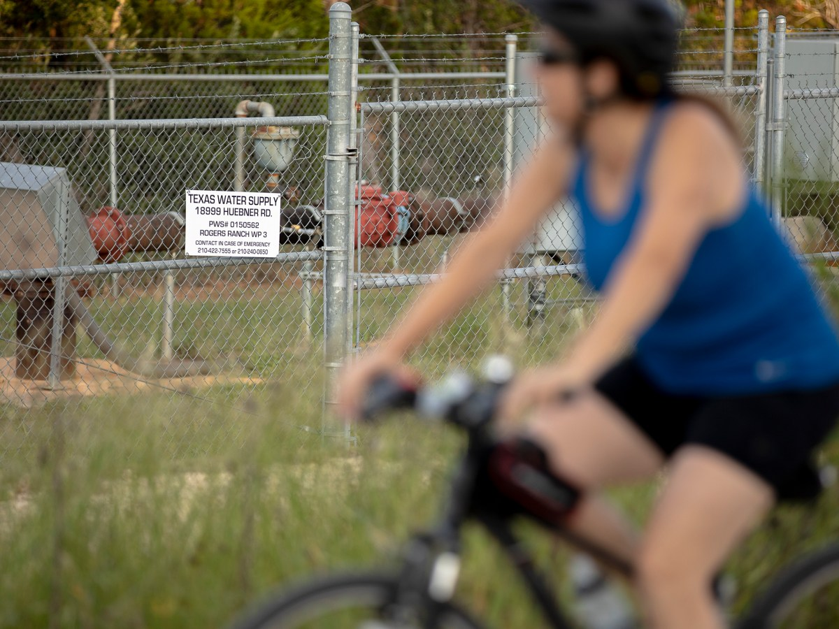 A bicyclist passes by a well owned and operated by Texas Water Supply along the Salado Creek Greenway trail in North San Antonio on Tuesday.