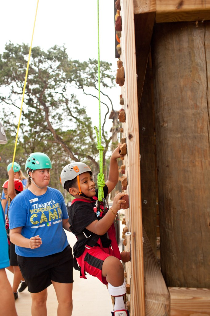 Devon Harrigan, right, climbs a rock wall with assistance from Torye Gleitz at Morgan's Wonderland Camp