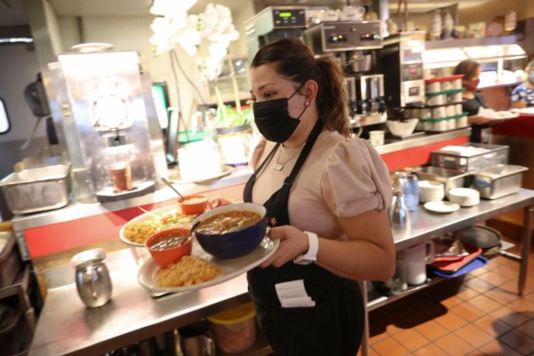 Nancy Dias, a waiter at Piadras Negras De Noche, brings out food during lunch service.