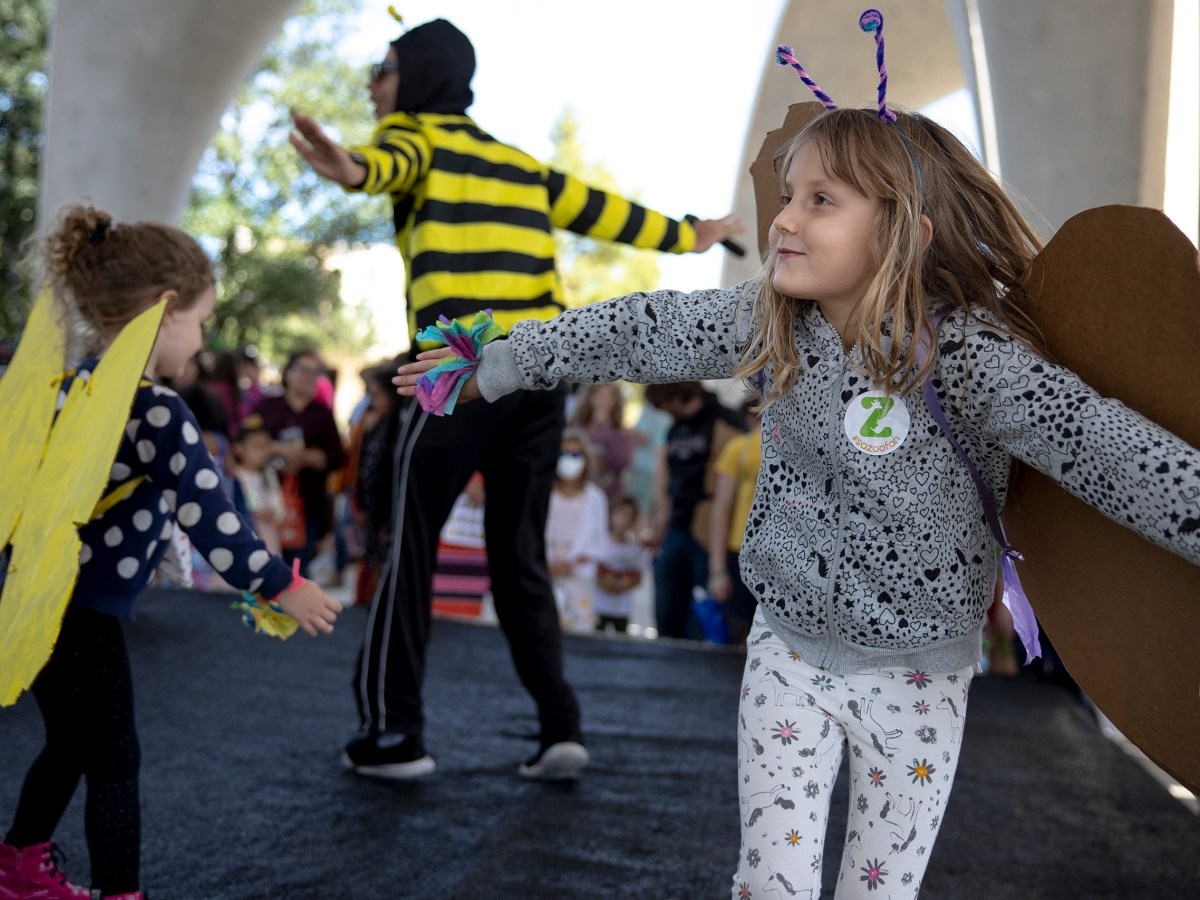 Nora Balmer, 6, right, dances with her sister, Mae, 3, while wearing handmade butterfly wings during the Monarch Butterfly and Pollinator Festival at Confluence Park on Saturday.
