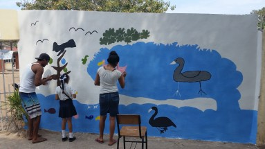 Helping 3rd grader Noemi paint her drawing, ´´Protect the birds of Boca´´