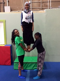 Teens from the Refugee Women's Alliance learn to work together balancing and sharing body weight in preparation for acrobatics.