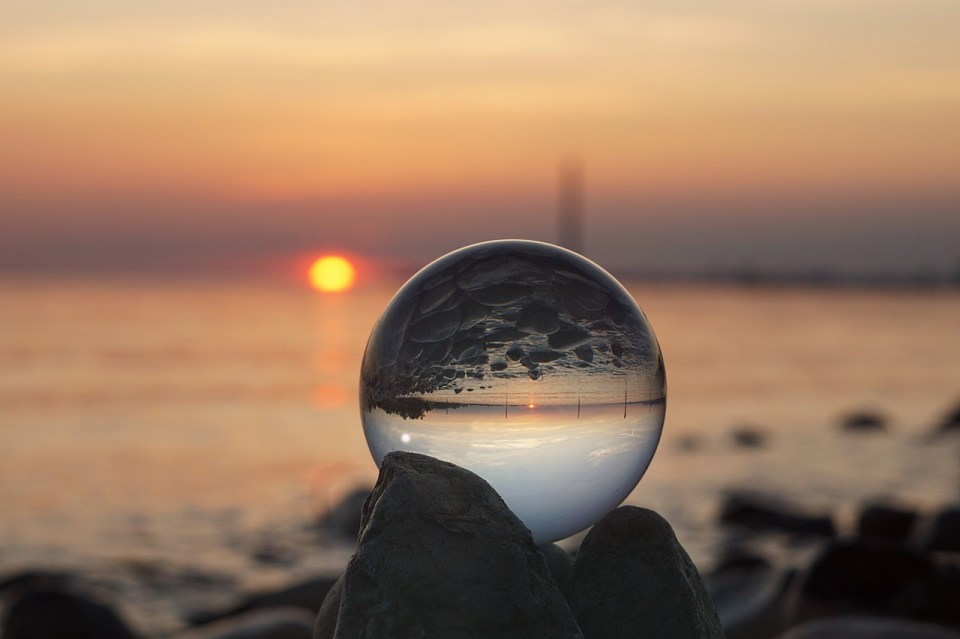 Photograph of a beach at sunrise through a clear glass sphere reflecting a rocky shore.