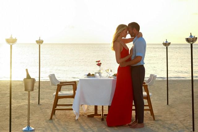 Couple bénéficie d'un dîner privé aux chandelles au bord de la mer