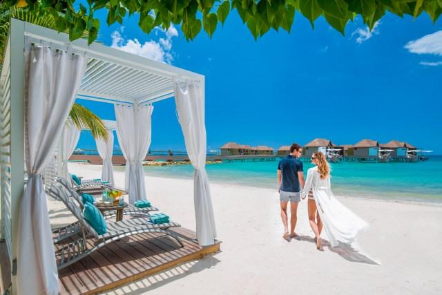 Couple marche le long d'une plage de sable blanc calme
