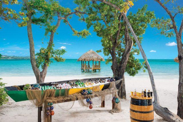 Canoë à bière se trouve sur une plage de sable blanc avec des eaux turquoises en arrière-plan
