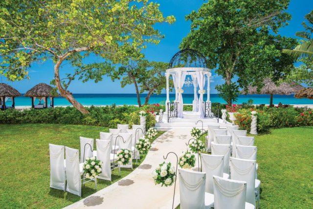 Cérémonie de mariage élégante mise en place sur une pelouse surplombant la mer des Caraïbes.
