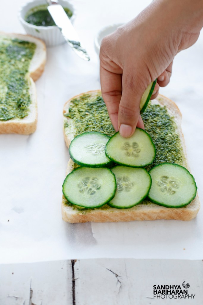 Placing Cucumber slices over spread coriander chutney on the bread.