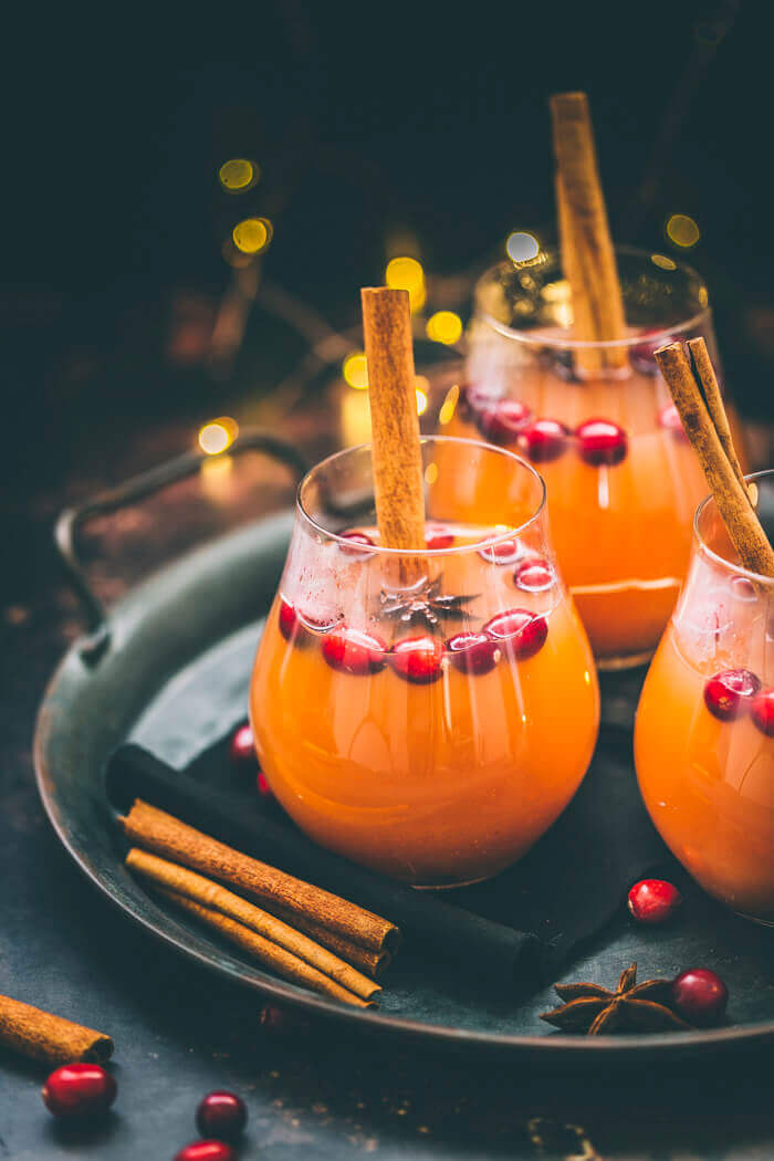 Apple cider served in glasses with a cinnamon stick