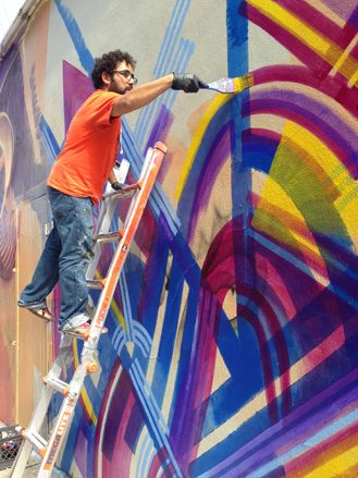 Artist Isaias Crow paints a mural adjacent to Chicano Park.